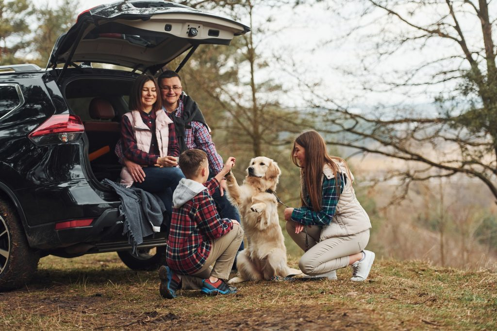 Happy family have fun with their dog near modern car outdoors in forest
