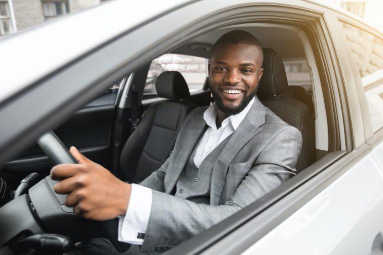 Handsome smiling black businessman driving luxury car
